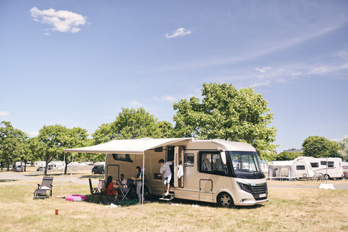 Family camping outside travel trailer at campsite against sky - MASF11025