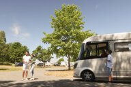 Teenage boy standing by mother in camper van while father and daughter reading map on road - MASF11034