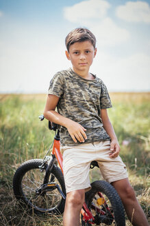 Portrait serious boy on bicycle in field - FSIF03727