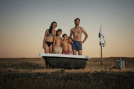 Portrait smiling family in bathing suits standing next to bathtub in rural field - FSIF03739
