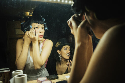 Female burlesque performers getting ready, applying makeup at dressing room mirror - FSIF03760