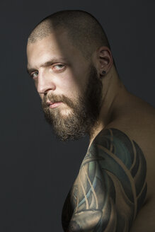 Portrait serious man with beard and tattooed shoulder - FSIF03763