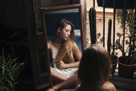 Mirror image of young woman sitting on the floor at home relaxing - LOTF00052