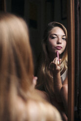 Beautiful young woman putting on lipstick in front of a mirror at home. Spain, Catalonia, Barcelona. - LOTF00055