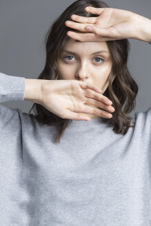 Portrait of brunette young woman, hands over her face - VGF00195