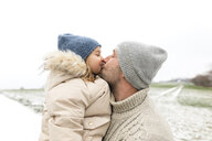 Father kissing daughter in winter - KMKF00680