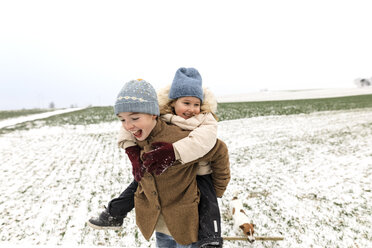Boy carrying happy sister piggyback in winter landscape - KMKF00683