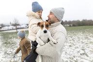 Wickede, NRW, Deutschland. Ein Vater spielt  mit seiner Tochter  und einem Jack Russell Terrier Hund  mit Schnee im Winter im Freien - KMKF00686