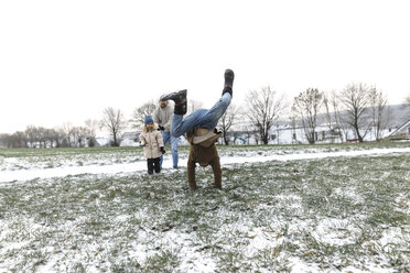 Boy doing a handstand on snowy field with family in background - KMKF00689