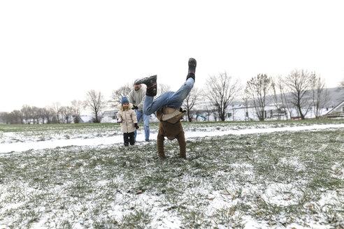 Wickede, NRW, Deutschland.Ein Teenager steht auf Hände auf dem Feld, sein Vater und Schwester sind im Hintergrund - KMKF00689