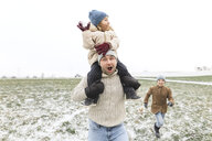 Wickede, NRW, Deutschland. Ein Vater spielt  mit den Kindern mit Schnee im Winter im Freien - KMKF00692