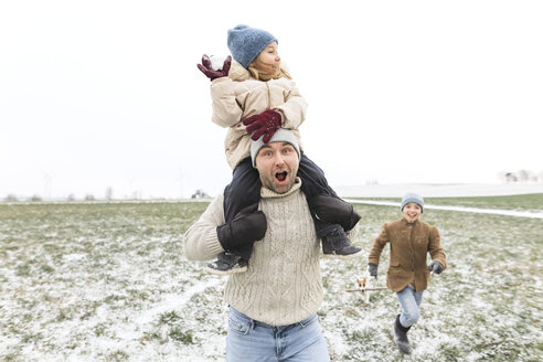 Happy father with two children in winter landscape - KMKF00692