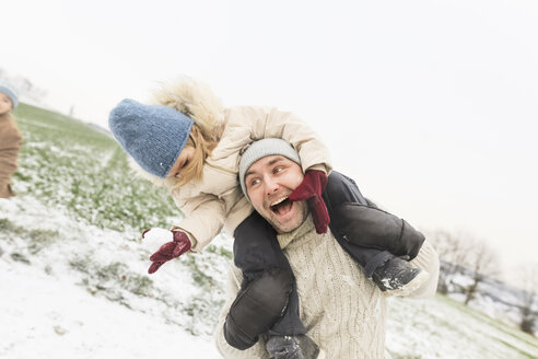 Playful father carrying daughter piggyback in winter landscape - KMKF00698