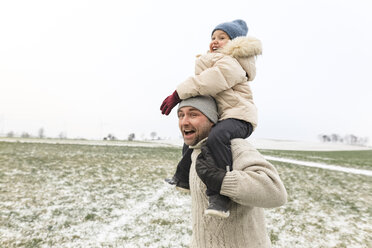 Playful father carrying daughter piggyback in winter landscape - KMKF00701