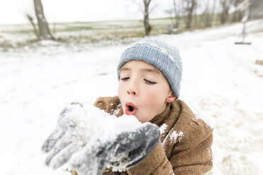 Boy playing with snow in winter - KMKF00707