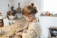 Little girl slicing bread in the kitchen - KMKF00713