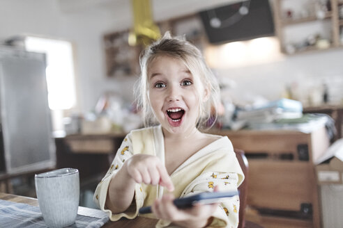 Portrait of excited little girl in the kitchen pointing at smartphone - KMKF00716