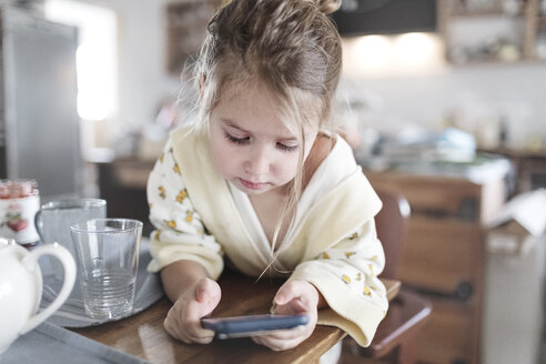 Wickede, NRW, Deutschland. Ein kleines lachendes Mädchen sitzt in der Küche mit einem Smartphone - KMKF00719