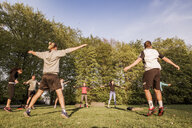 Friend with arms outstretched exercising on field in park - ASTF02244
