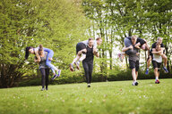 Man and woman carrying friends while running on field - ASTF02271