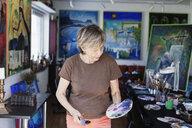 Senior female artist holding palette and paint brushes in studio - ASTF02289