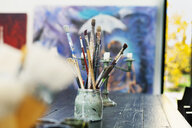 Paintbrushes in container on table at art studio - ASTF02292