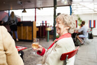 Senior woman holding wineglass and smiling while sitting at restaurant with friends - ASTF02373