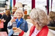Senior women holding wineglasses while sitting at restaurant - ASTF02376