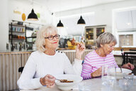 Senior women eating food on table at restaurant - ASTF02382