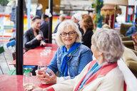 Senior women holding wineglasses while sitting at restaurant - ASTF02406