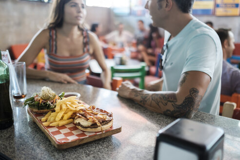 Hamburger and French fries on counter in a bar with couple socializing in background - ABAF02234