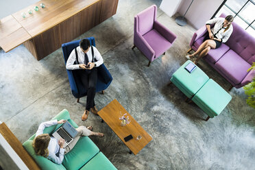 Top view of business colleagues working on laptop and smartphone in coworking space - SBOF01547