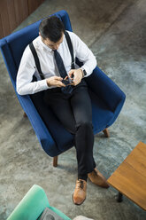 birds view of dark-haired business man working on smartphone on blue armchair in coworking space - SBOF01559