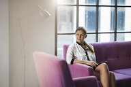 Young businesswoman sitting on violet couch with tablet - SBOF01562