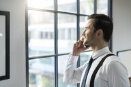 Smiling businessman looking out of window in office talking on cell phone - SBOF01565