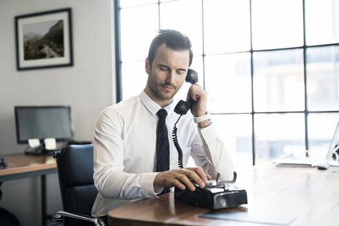 Businessman in office using vintage retro telephone - SBOF01568