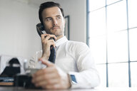 Businessman in office using vintage retro telephone - SBOF01571