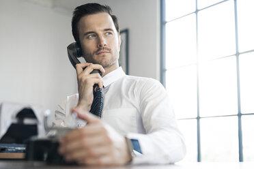 Businessman in office using vintage retro telephone - SBOF01571