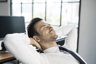 Smiling businessman in office leaning back - SBOF01574