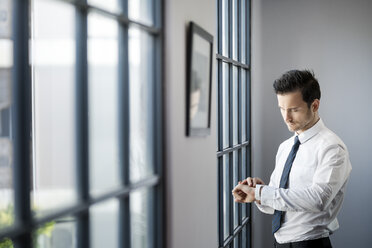 Businessman checking smartwatch in front of large office window - SBOF01577