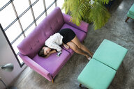 Top view of tired businesswoman sleeping on violet couch in office - SBOF01580