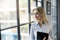 Confident businesswoman with tablet in office looking out of window - SBOF01583