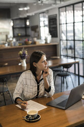 Young businesswoman in a cafe writing on paper and working with laptop on wooden table - SBOF01586