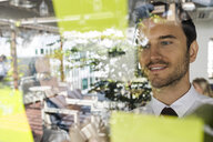 Businessman with colleague brainstorming with post-its on window front - SBOF01598