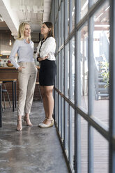 Two female colleagues talking in cafe in front of windows - SBOF01604