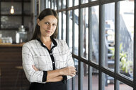 Portrait of attractive businesswoman in front of windows - SBOF01607