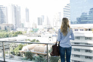 Rear view of blond woman standing on balcony in the city - SBOF01610