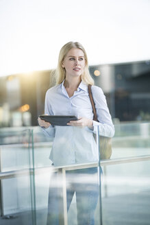 Blond woman with tablet standing at glass railing in the city - SBOF01613