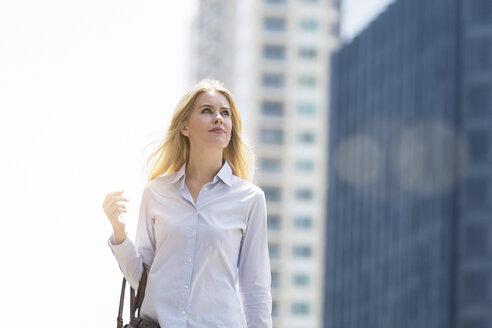 Blond woman with handbag walking through the city - SBOF01616