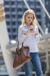 blonde woman with handbag checking smartphone in city - SBOF01619